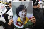A supporter holds a portrait of South Korean President Park Geun-Hye during a rally opposing her impeachment in Seoul. / Lee Jin-Nan